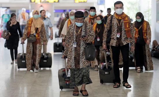 أشخاص يرتدون أقنعة يمشون في مطار باندارانايكي الدولي