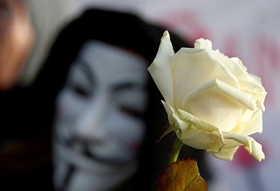 متظاهر يرتدي قناع جاي فاوكس يحمل وردة فى مظاهرة خلال اليوم 31 من الإضراب فى فرنسا