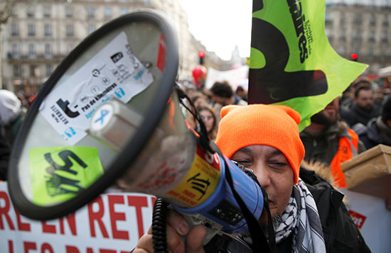 متظاهر يحمل مكبرًا صوتيًا في مظاهرة خلال اليوم الحادي والثلاثين على التوالي من الإضراب
