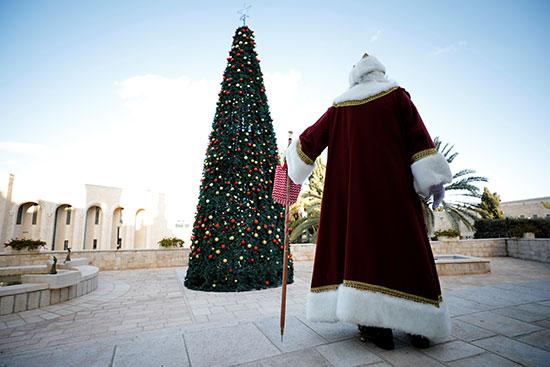 رجل يرتدى زى سانتا كلوز يسير بجوار شجرة عيد الميلاد