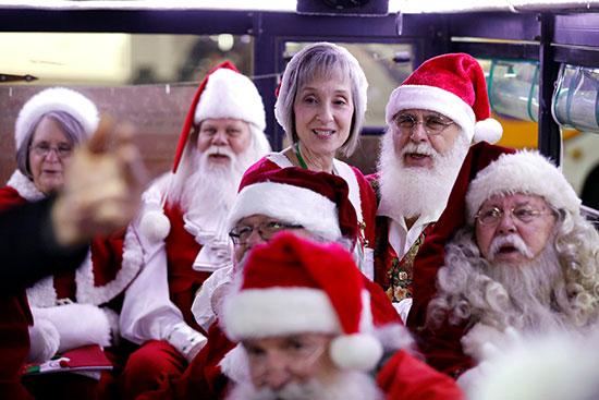 أشخاص يرتدون ملابس سانتا كلوز يغنون من داخل حافلة أثناء طريقهم لزيارة مدينة القدس القديمة