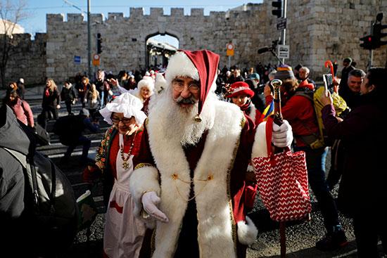 رجل يرتدى زى سانتا كلوز يمشى خارج المدينة القديمة بالقدس