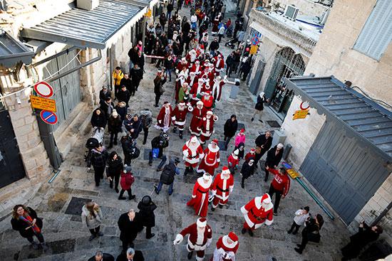 مجموعة من الأشخاص من جميع أنحاء العالم يرتدون ملابس سانتا كلوز