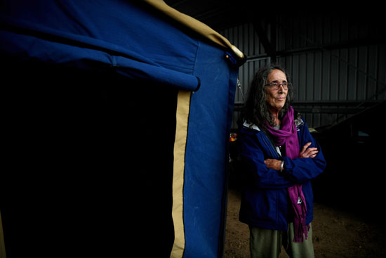 سيدة تقف بجانب خيمة بمركز الإخلاء عقب إحتراق منزلها