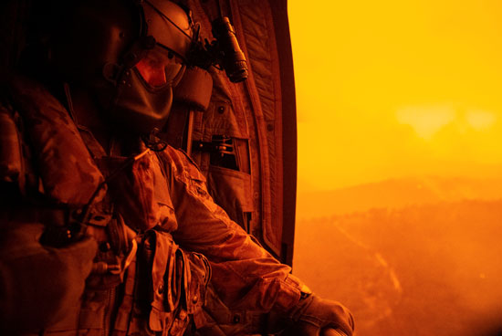أحد الجنود من داخل طائرة الأطفاء يرصد حرائق الغابات فى أستراليا