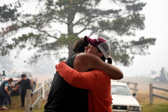 رجل وزوجته يحتضنون بعضهما بعد إحتراق منزلهما جراء حرائق أستراليا