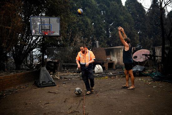 سكان كوبارجو يلعبون كرة السلة بجانب منزلهم المحترق