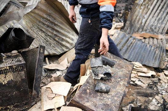 أحد سكان كوبارجو يمر عبر بقايا منزله المدمر بسبب الحرائق