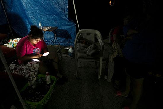 الناس يستريحون في معسكر مؤقت خارج مبنى شقتهم بعد زلزال في يوكو