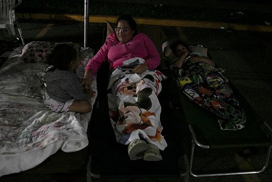 سيدة تجلس وسط طفلتيها فى معسكر إيواء