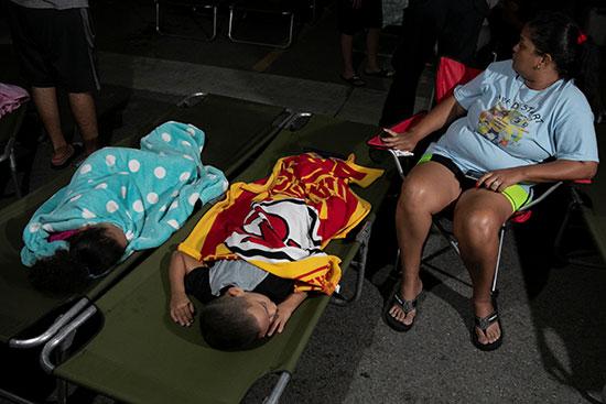سيدة تسهر امام طفليها النائمان فى معسكر إيواء