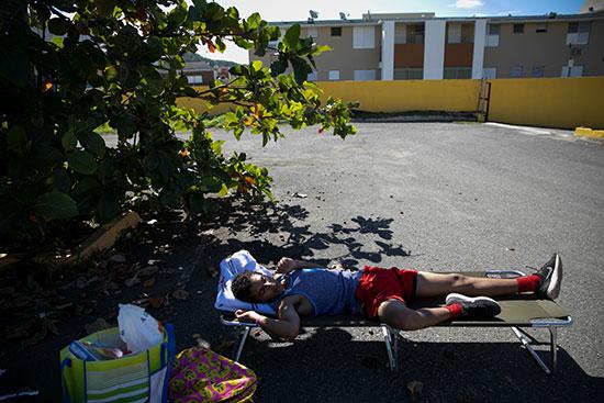 صبي ينام على سرير في معسكر في معسكر إيواء مؤقت في مجمع رياضي