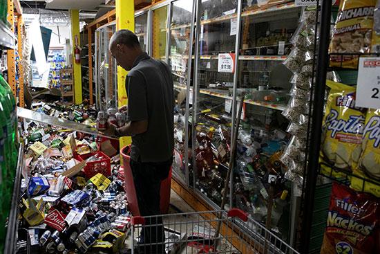 عامل ينظف متجراً بعد زلزال في جوانيكا