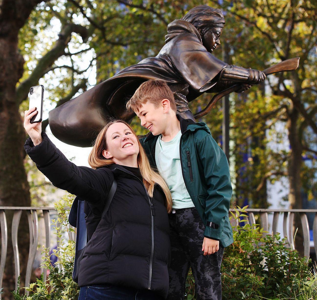 سيلفى طفل ووالدته مع تمثال هارى بوتر