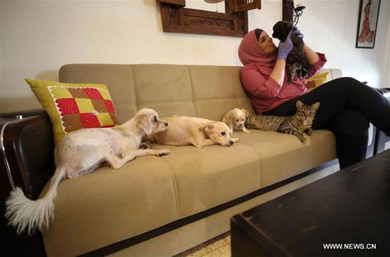 مها منصور مع القطط والكلاب التي ترعاها