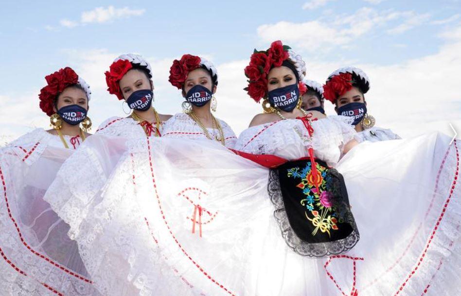 راقصون من شركة رقص مكسيكية محلية يرتدون أقنعة الوجه تدعم بايدن