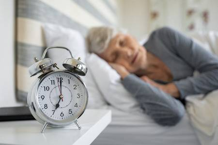 107595478-closeup-of-alarm-clock-with-senior-woman-in-deep-sleep-at-home-old-woman-sleeping-in-bed-next-to-ala