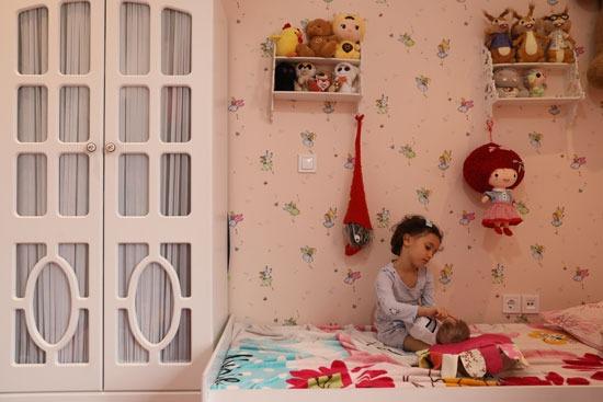 طفلة إيرانية تلعب مع دمية تعتبرها أختها