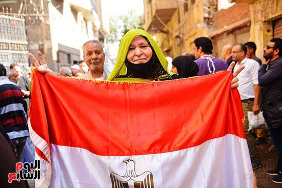 ناخبة-ترفع-علم-مصر-قبل-الادلاء-بصوتها-في-الانتخابات-البرلمانية