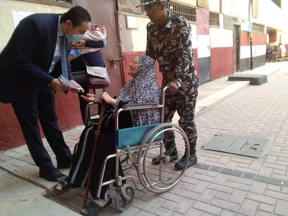 رئيس لجنة فرعية يخرج لسيدة مسنة لمساعدتها للإدلاء بصوتها بالإسكندرية