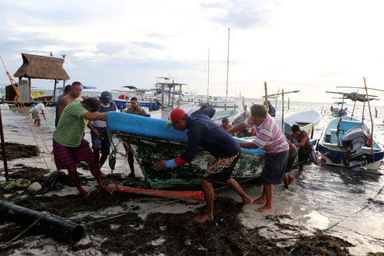 الصيادون يسحبون قواربهم من الشاطئ