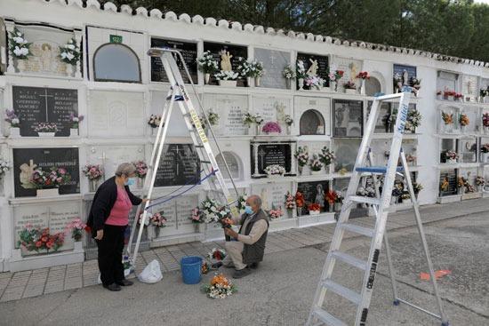 يقوم الناس بإعداد الزهور لوضعها على شاهد قبر أقاربهم