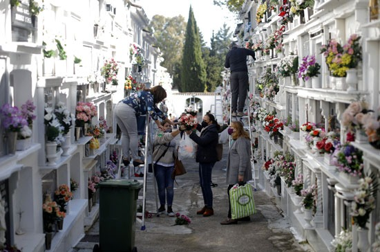 السيدات يضعن الزهور احتفالا بعيد الموتى