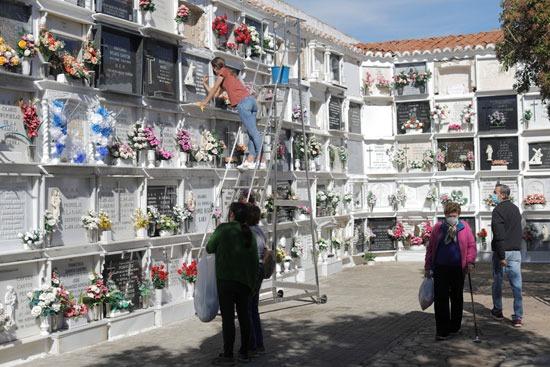 امرأة تعد شاهدة قبر لتكريم قريبها في مقبرة قبل عيد جميع القديسين