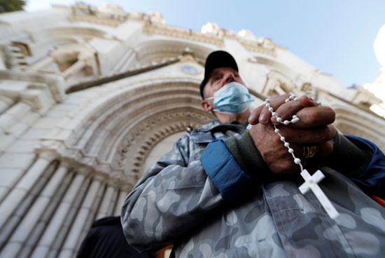أحد الأشخاص يسمك بالصليب أمام الكنيسة