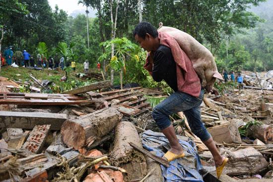 رجل يحمل خنزير نجى من الفيضانات