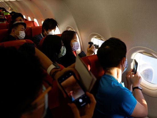 يلتقط الركاب صورًا لمناظر جوية لهونج كونج