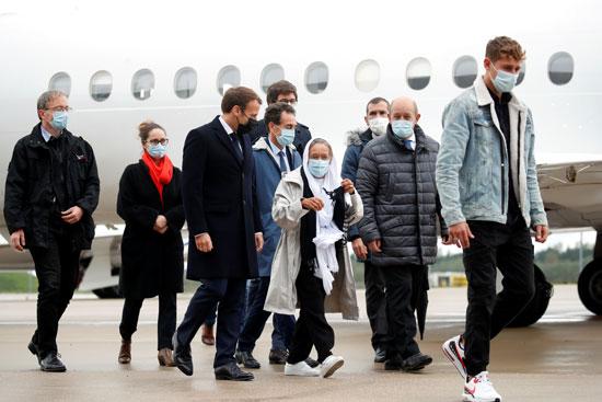 ماكرون ووزير الخارجية جان إيف لودريان يرافقان موظفة الإغاثة الفرنسية صوفي بترونين