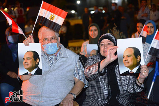 رجل وزوجته يرفعان صورة الرئيس السيسى وعلم مصر