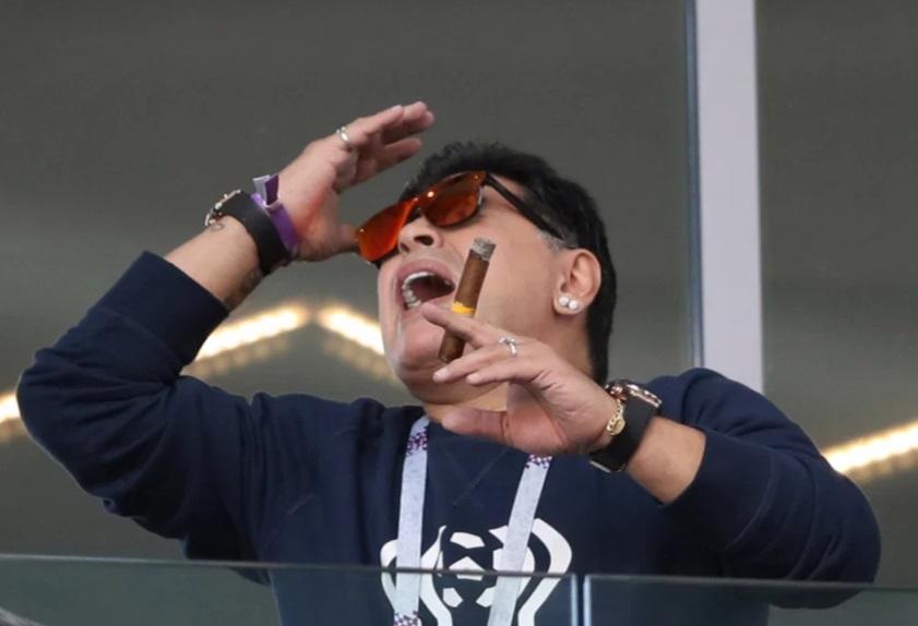 مارادونا يحمل السيجار اثناء مشاهدة لقاء الارجنتين وايسلندا بمونديال 2018