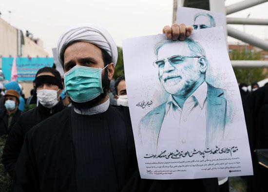 رجل يحمل صورة محسن زاده