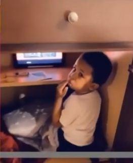 الطفل يجلس داخل خزانة المطبخ