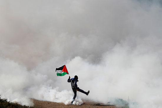 شاب فلسطيني يحمل العلم وسط الغاز