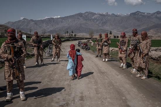 طفلان يسيران أمام أعضاء من وحدة طالبان في أفغانستان