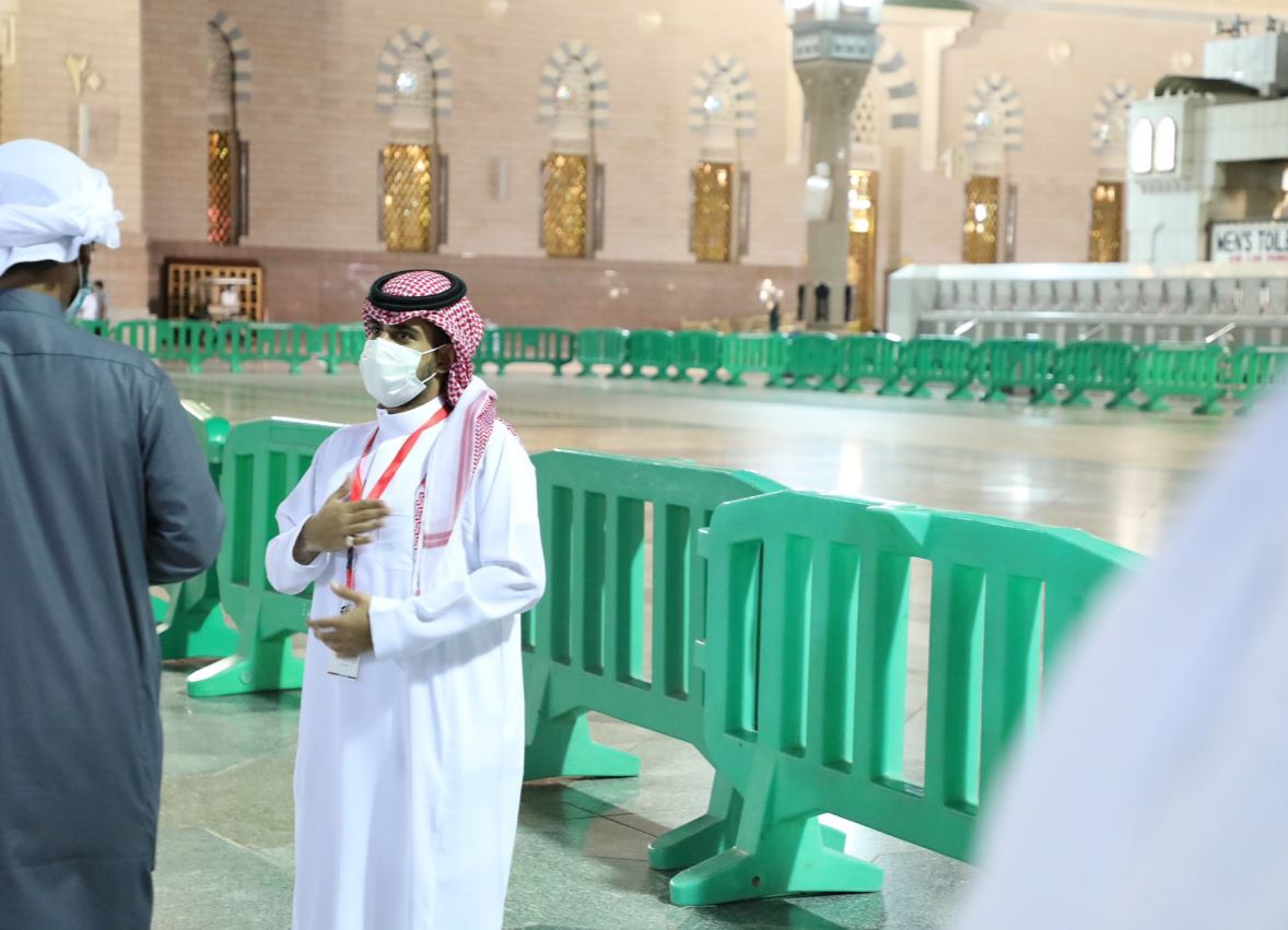 أحد المتطوعين مع مصلي بالمسجد النبوي