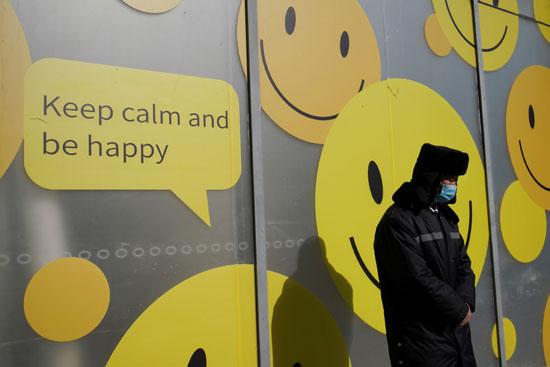 فرد أمن يرتدى قناع وجه يقف بجانب مركز تجارى فى بكين