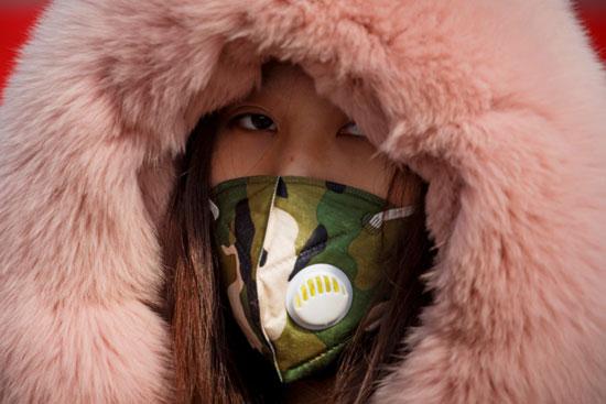 امرأة ترتدى قناع الوجه عند نقطة تفتيش