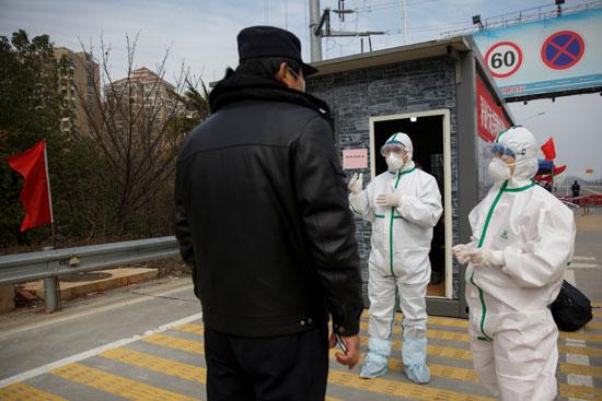 موظفو مستشفى يرتدون يتحدثون إلى أحد ضباط الشرطة عند نقطة تفتيش