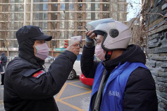 ضابط أمن يأخذ قياس درجة حرارة الجسم لعامل توصيل