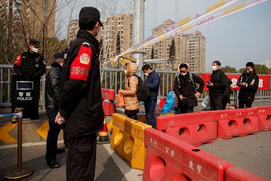 صينين من مقاطعة هوبى يصطفون عند نقطة تفتيش