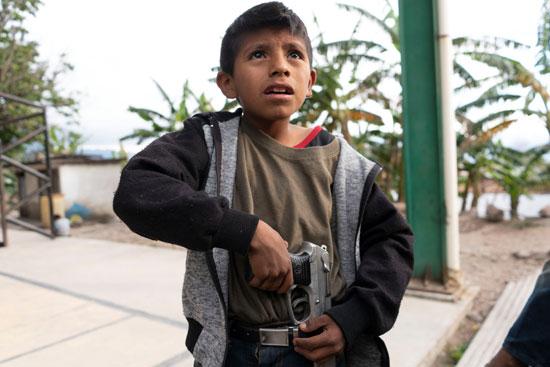 طفل مكسيكى يحمل مسدسا حقيقيا