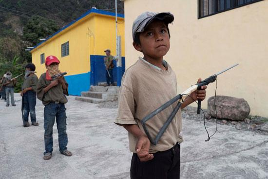 يحمل الأطفال أسلحة اللعب وهم يتدربون على الأسلحة على الطريقة العسكرية