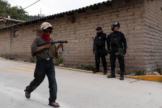 طفل يسير عبر ضباط شرطة الولاية يحمل بندقية لعبة