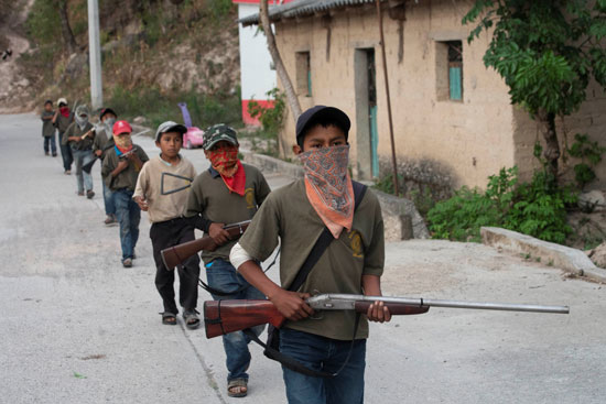 أطفال يمشون في صف واحد  يحملون أسلحة حقيقية