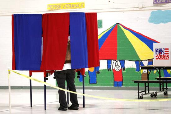 ناخب يقف في كشك للتصويت في مدرسة في نيو هامبشاير الأمريكية بمانشستر