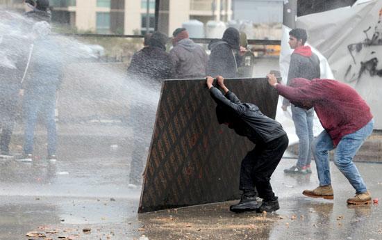 متظاهرون-يحتمون-من-رشاشات-المياة-التى-تطلقها-الشرطة
